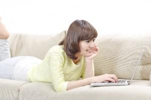 ソファでパソコンを操作する女性